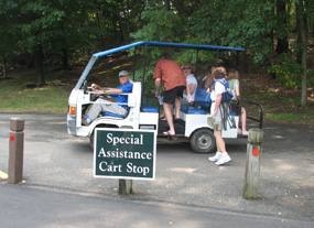 Patrons getting on a cart in the parking lot for a ride to the main gate.