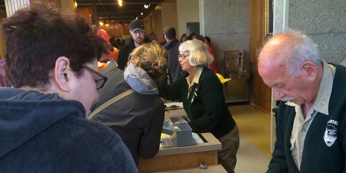Volunteers helping visitors at the front desk of the visitor center