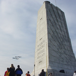 visitor at 60 ft. granite monument watching four military planes.