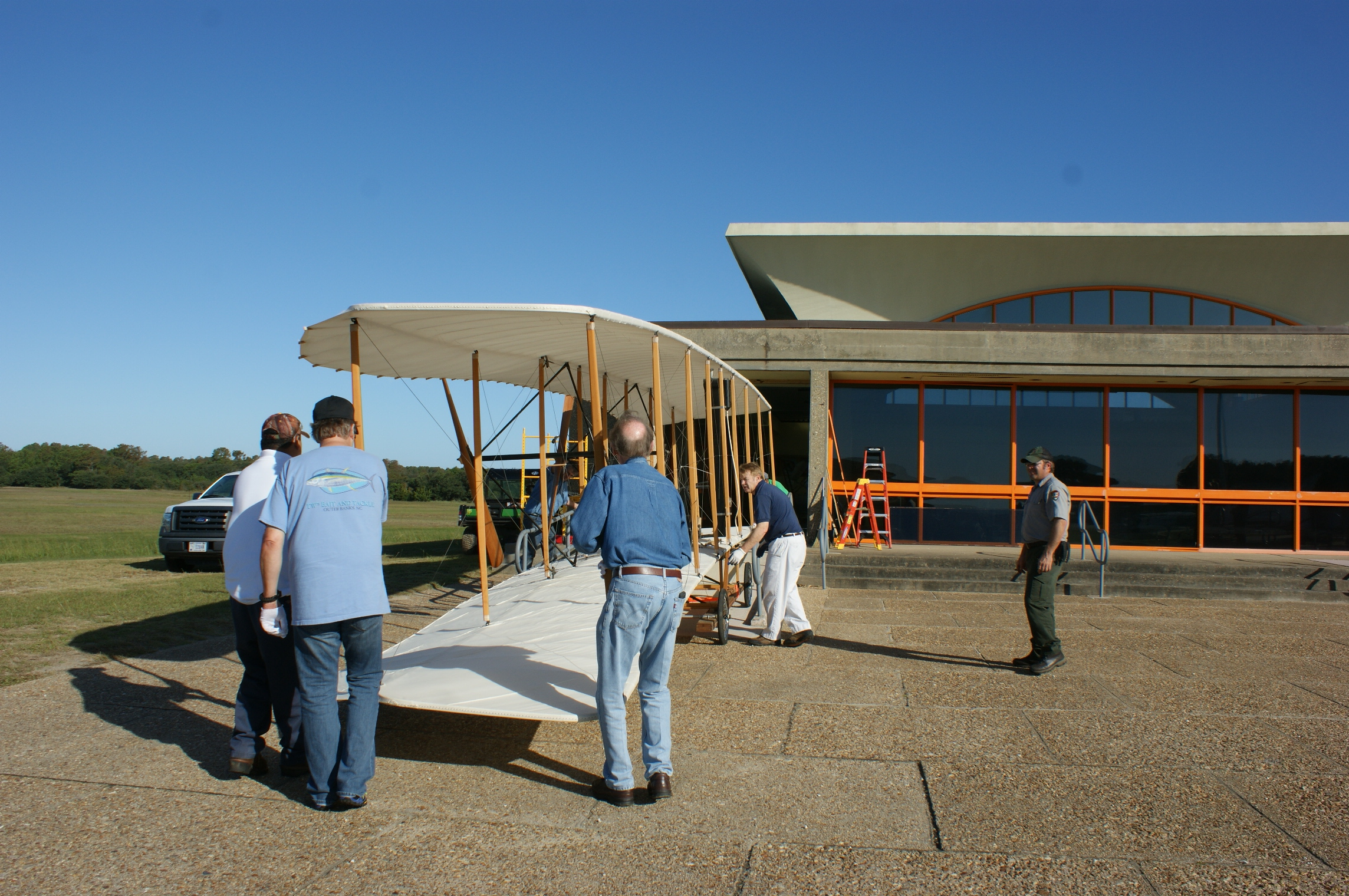 Moving crew carefully moving the Wright brothers 1903 Flyer from the visitor center.