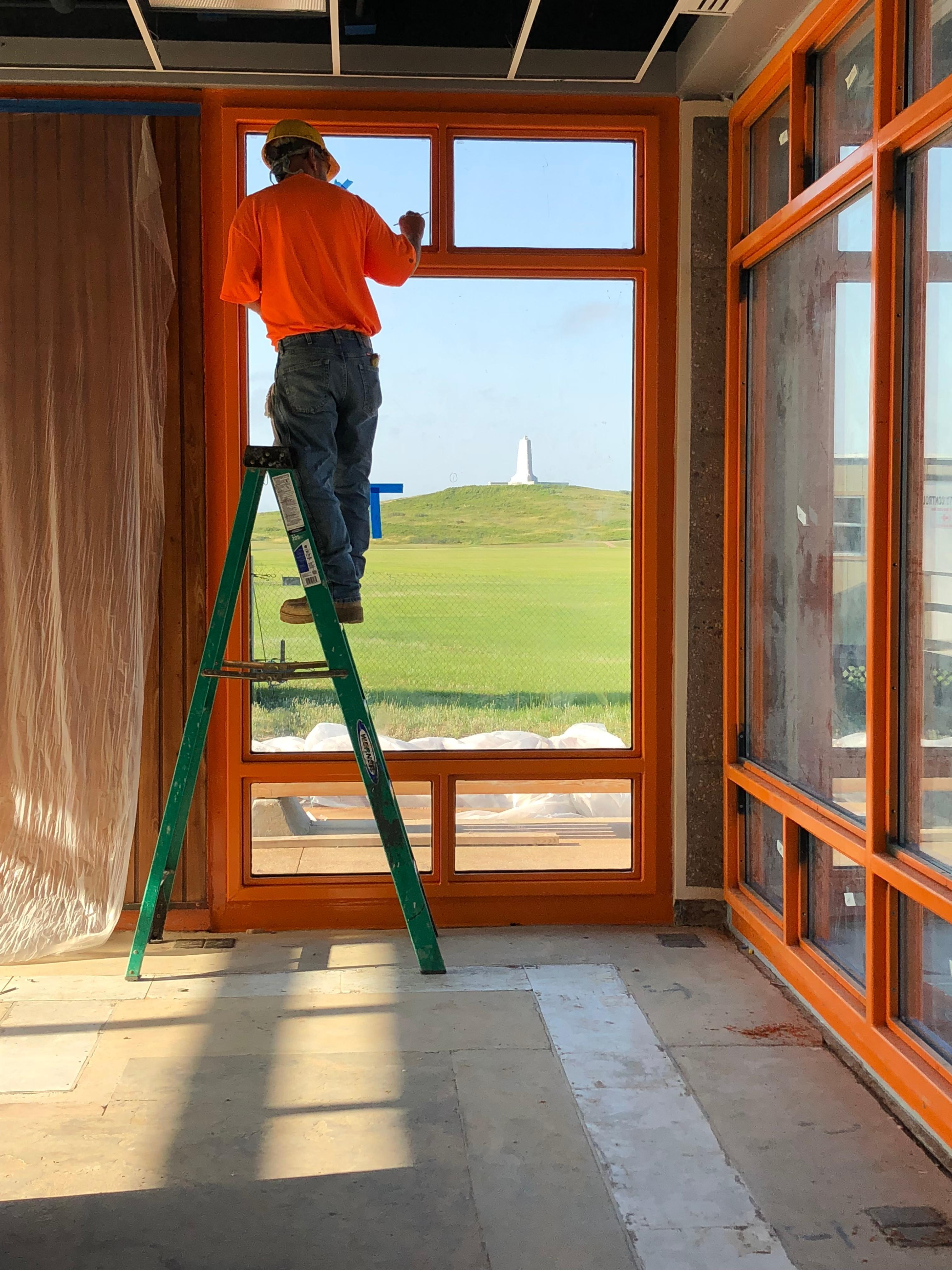 Contractor working on custom fabricated window frame with view of the Wright Brothers National Memorial monument.