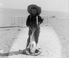 Local boy, Tom Tate, stands in front of the 1900 glider with a drum fish.