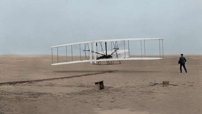 Early bi-plane lifting off the sand