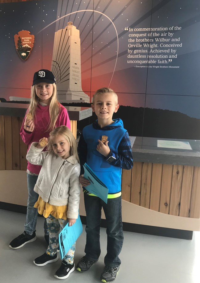 Three young children stand in front of a front desk proudly wearing their junior ranger badges. An image of the Wright Memorial is pictured behind them.