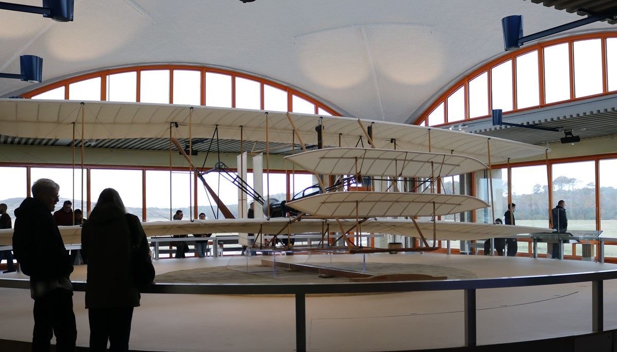 Visitors walking around reproduction of 1903 Wright Flyer inside our visitor center