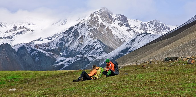 Two backpackers sitting in a high alpine meadow surrounded by mountains.