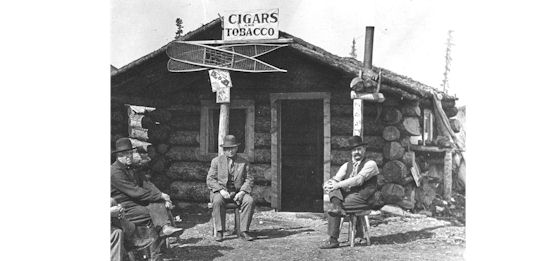 Historic photo of men sitting on stools in front of log cabin store.