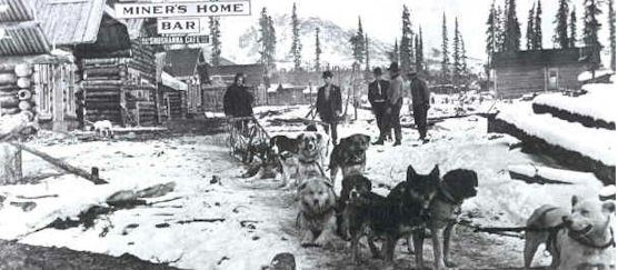 Historic photo of dog sled team with people in small town with wood buildings.