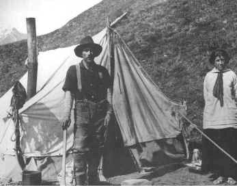 Historic photo of miner with woman in front of canvas tent.