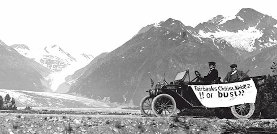 "Early 1900s automobile with ""Faribanks, Chitina, Valdez, or bust"" hand written banner on it and mountains and glacier in the background."