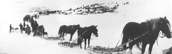Historic photo of miners travelling in snow covered Thompson Pass with horses, sleds, and early bicycles.