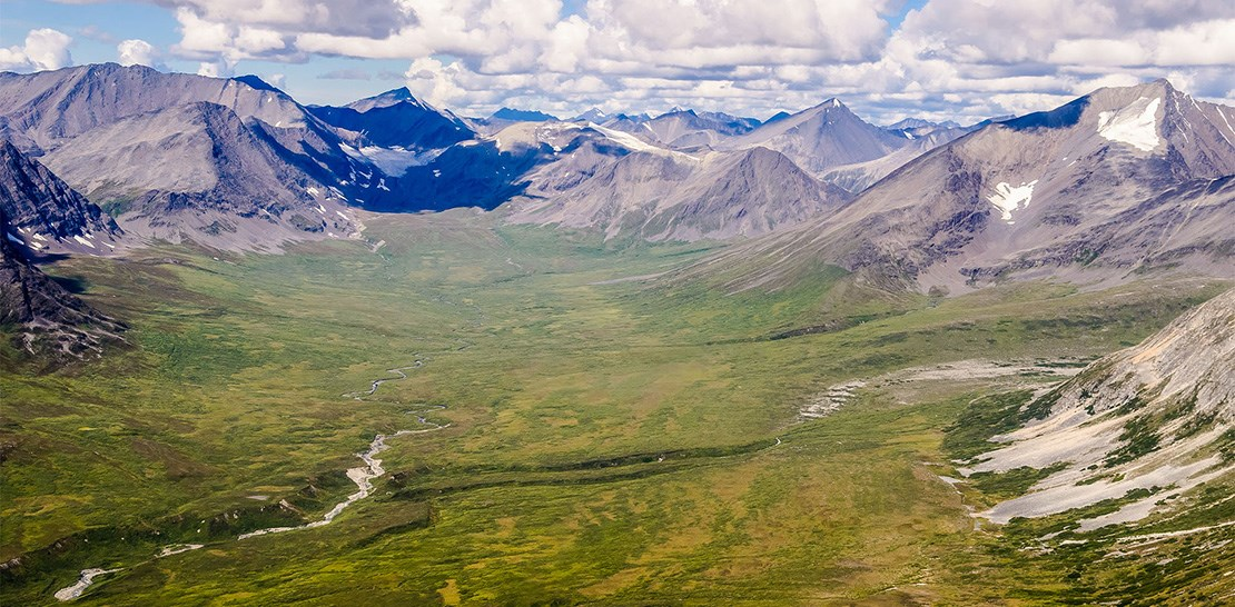 Photo of green tundra valley surrounded by rocky mountains that contain glaciers.