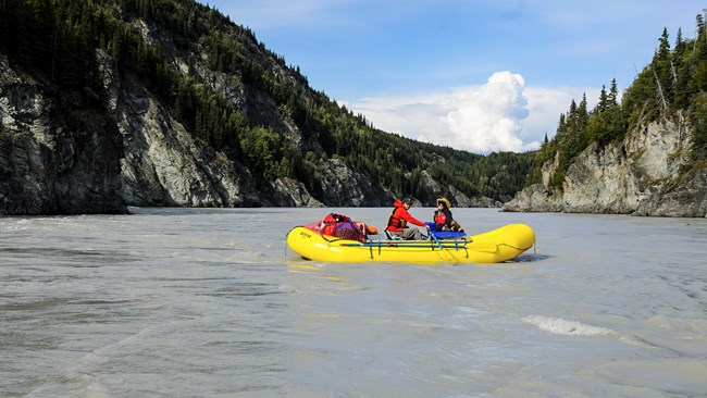 Two people in a rubber boat rafting the Copper River through a canyon.