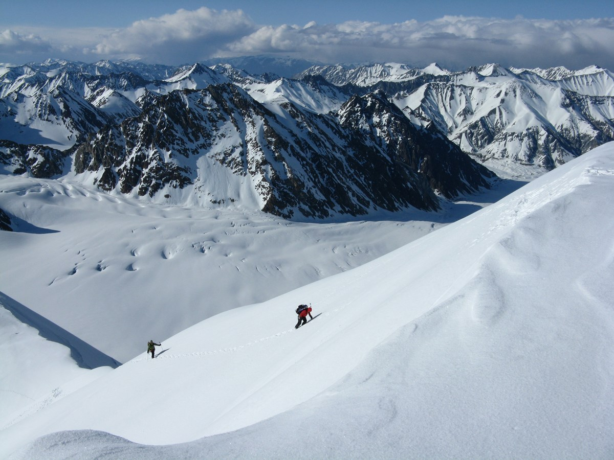 two people traversing the glacier on skiis