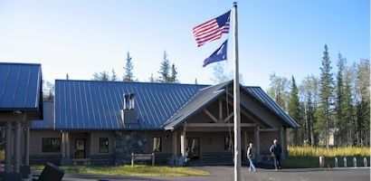 flagpole with american flag and alaska state flag flying in front of a large wood building