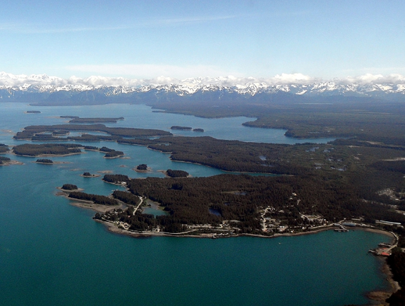 Aerial view of the town of Yakutat with forest, ocean, and islands in the foreground and snow capped mountains in the background.