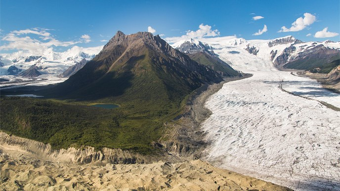 View of glaciers with forest, mountains, and cloudy blue skies in background.