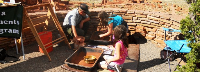 Two girls sifting artifacts with a park archeologist