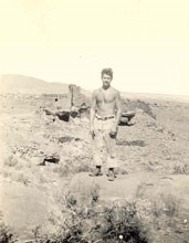 A CCC worker standing in front of Wupatki Pueblo