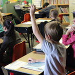 Student raising hand in classroom.