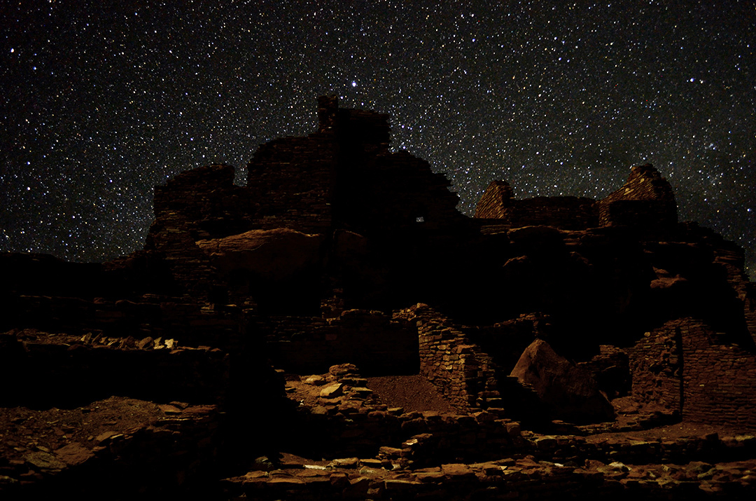 a large stone pueblo building beneath a dark sky filled with stars