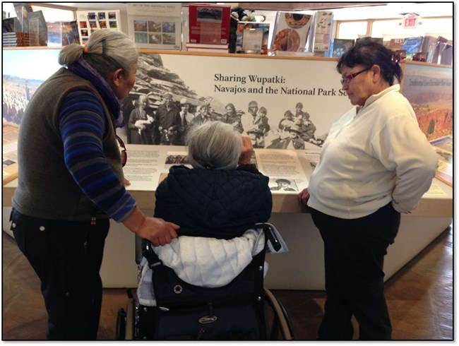 Three Navajo women, one in a wheelchair, talking in front of a museum exhibit.