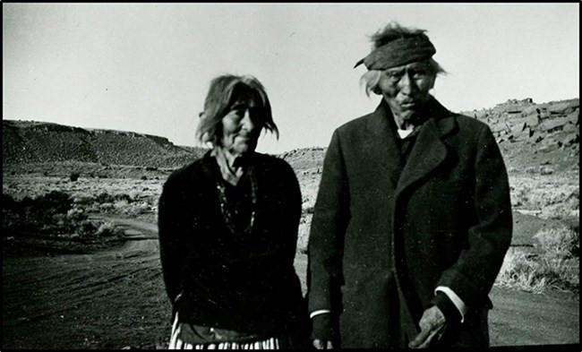 a Navajo woman and man stand together in a desert wash