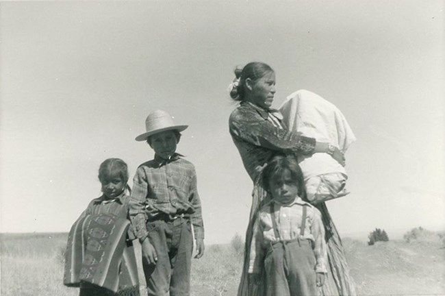 a Navajo woman in the desert with four young children, one in a traditional cradle board