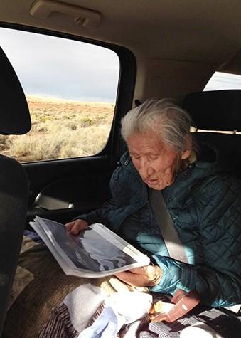 an elderly Navajo woman looking at historic photos inside a vehicle