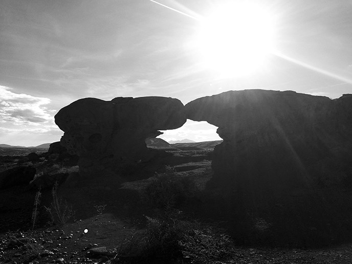 afternoon sunshine glares brightly over a natural stone arch in the desert
