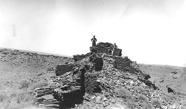 Two men standing on the top of Wupatki pueblo in the early 1900s before archeologists did any reconstruction or excavation. Only partial walls existed and the remaining stones were on the ground below.