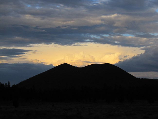 The Sunset Crater cinder cone volcano is nearly black, contrasting with billowing white thunder clouds and smaller grey clouds in the sky