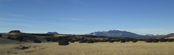 The snow-capped San Francisco Peaks tower over the Wupatki Basin grassland.