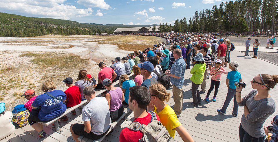 Hundreds of people waiting for an August eruption of Old Faithful