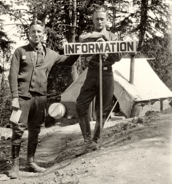 Two ranger naturalists behind an information sign with a small tent in the background, circa 1925.