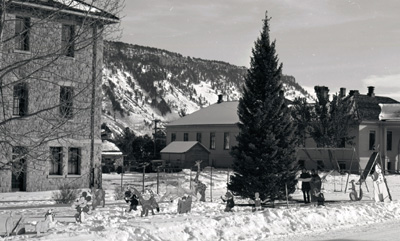 Though a bit later than the 1899 celebration described, this photo shows that ensuring local children had a merry Christmas continued for the next 100 years. Tree and decorations outside of the Administration Building in Mammoth, ca. 1960? Photo: #YELL 19967