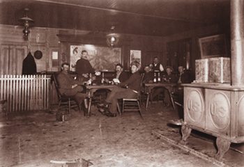 Soldiers relaxing with cards and drinks in the post exchange, Fort Yellowstone, Wyoming, circa 1900. Yellowstone Park Museum Collection, YELL 36921