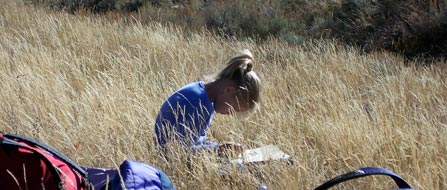 A young student works on a paper in a field of grass
