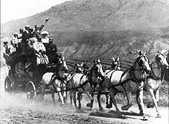 "Six-horse ""Tally-Ho"" stagecoach enroute from the Northern Pacific Railroad depot in Gardiner, Montana to Mammoth Hot Springs, taken about 1910. The seats on the roof were reportedly the most sought after by visitors; unfortunately, none of the examples in the park's museum collection retain these seats."
