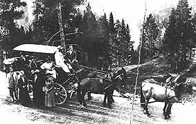 (YELL 36451) Driver and passengers posed with a four-horse Yellowstone Observation Wagon similar to the vehicle in the park's museum collection.