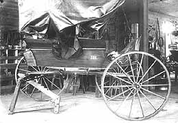 (YELL 41295) Two-seat surrey very similar to the vehicle in the park's museum collection. The vehicle appears to be in the blacksmith's shop for repairs to one of the wheels.