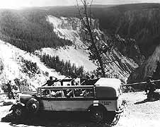 (YELL 96222) Tourists at the Grand Canyon of the Yellowstone near Artist Point in YPT Co. bus # 352, the same 1931 National Park Bus in the museum collection. Note the canvas top rolled back to allow the visitors an unobstructed view.
