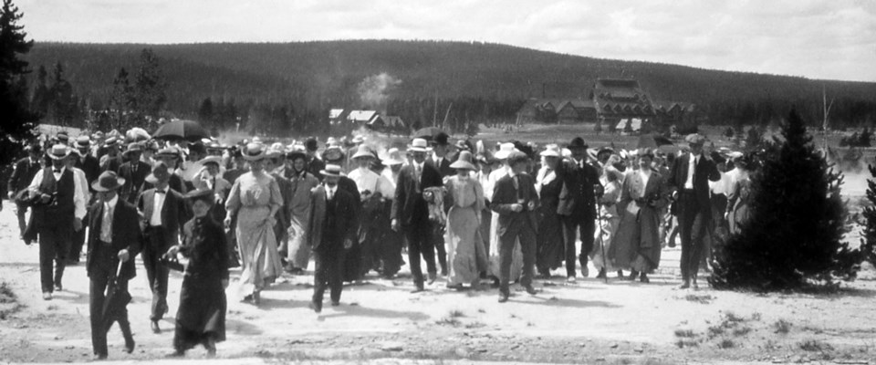 A historic photo of a large group of visitors walking away from the Old Faithful Inn.