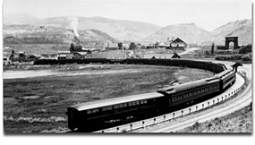 Historical photo with train pulling into Gardiner depot and Roosevelt Arch in the background.