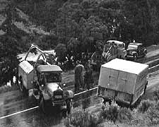 (YELL 27053-1) Accident scene in Gardner Canyon, 1952. The vehicle at left is Yellowstone Park Transportation Company Service Truck #937, and was used to help recover a car that had plunged into the river.