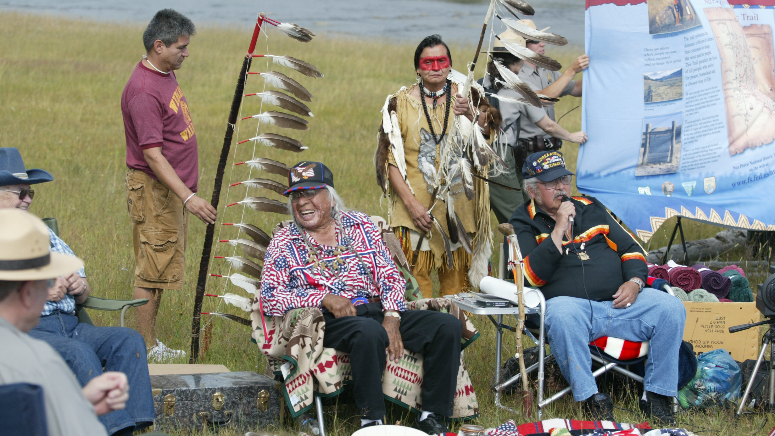 Nez Perce tribe members and NPS Rangers sit together during a commemoration of the Nez Perce Trail.