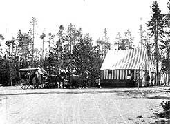 (YELL 90058-2) Shaw & Powell Camping Company group at a tent camp in Yellowstone. The Studebaker mountain stage at left is virtually identical to the example in the park's museum collection. (Montana Historical Society)