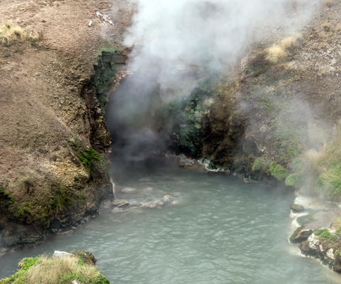 Steam rises from a large vent in a hillside above blue water