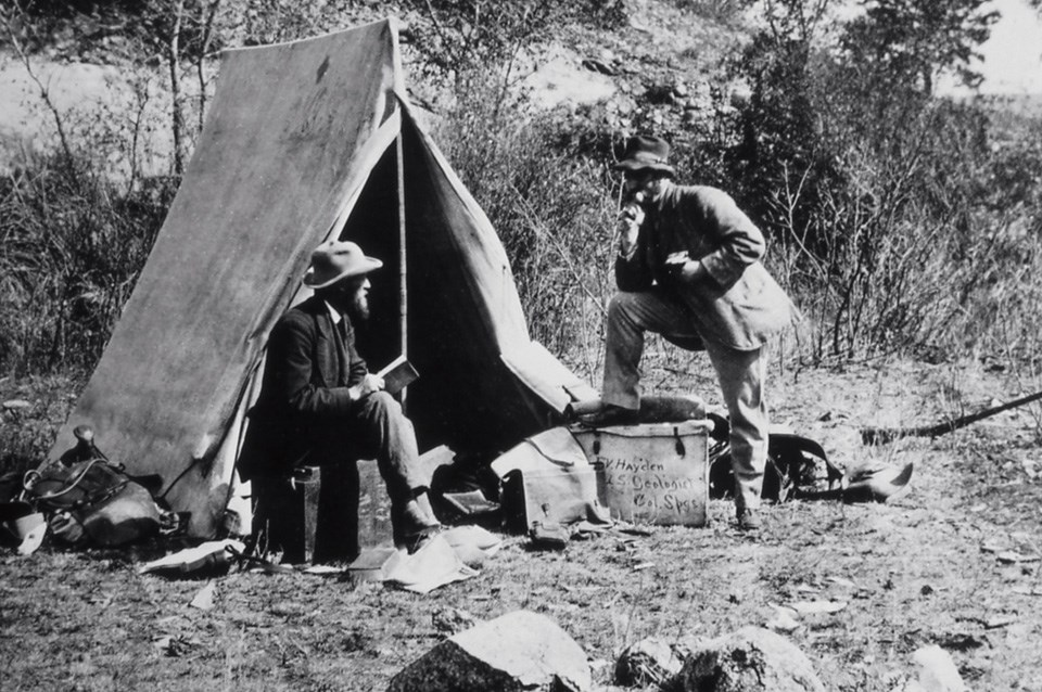 An historical photo of two men talking in front of a canvas tent.
