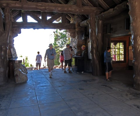 People walk through a breezeway between a stone building's wings